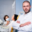 Stock Photo: Friendly male dentist with assistant and patient at dental clinic