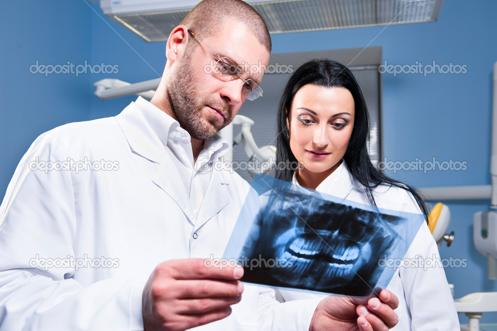 Dentist and assistant checking x-ray at dental clinic — Stock Photo #9478545