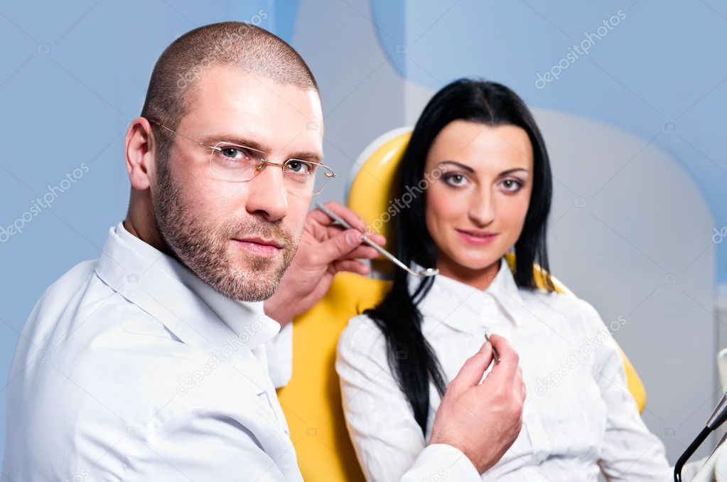Friendly male dentist with smiling patient at dental clinic — Stock Photo #9478568