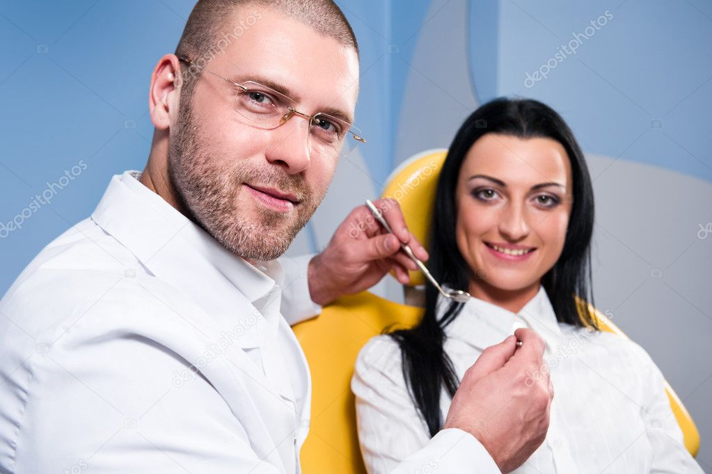 Friendly male dentist with smiling patient at dental clinic — Stock Photo #9478571