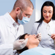 Male dentist with assistant and patient at dental clinic — Stock Photo #9511004