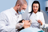 Male dentist with assistant and patient at dental clinic — Stock Photo