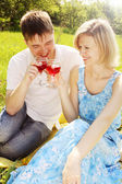 Couple in meadow with wine — Stock Photo