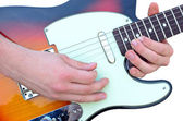 Closeup on hands playing guitar isolated on white — Stock Photo