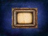 蓝色 grunge 墙上的空金色框架 — 图库照片