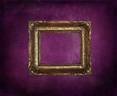 Antique picture frame on purple grunge wall — Стоковое фото