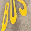 Yellow Bus sign painted on the asphalt - ストック写真