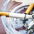 Burning cigarette in ashtray — Stock Photo