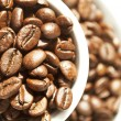 Cup full of coffee beans isolated on white background — Stock Photo #8524934