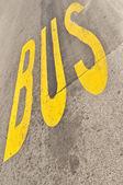 желтый автобус знак окрашен на асфальте — Стоковое фото