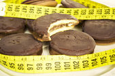 Chocolate cookies and measure tape — Stock Photo