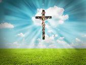 Jesucristo en cruz irradia luz en el cielo sobre paisaje — Foto de Stock