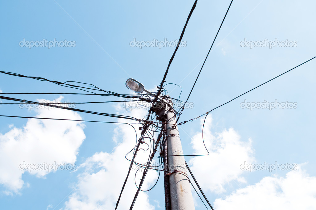 Old holder of the electrical installation with lighting against the sky — Stock Photo #8526567