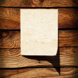 Empty grunge paper on wooden wall — Stock Photo
