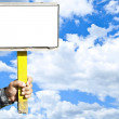 Man holding blank sign over blue sky with space for your text — Stock Photo #8539333