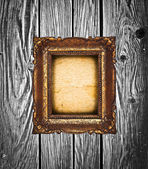 Vintage golden frame on wooden wall — Stock Photo