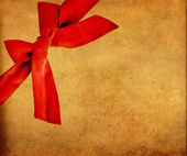 Red bow on grunge paper card — Stock Photo
