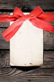 Empty paper with red bow on wooden background — Stock Photo