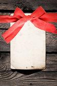 Tomt papper med röd rosett på trä bakgrund — Stockfoto