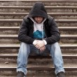 Stock Photo: Sad teenage boy with hood sitting on stairs
