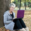 Beautiful young woman using laptop at outdoor — Stok fotoğraf