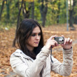 Beautiful girl taking photo with camera — Stock Photo