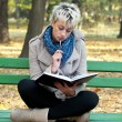 Beautiful girl studying outdoors reading a book — Stock Photo