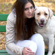 Beautiful girl and her dog sitting on bench in autumn park — Stock Photo