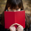 Stock Photo: Beautiful girl hiding behind book