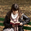 Beautiful woman sitting on a park bench and reading a book — Stock Photo