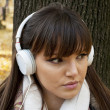 Young attractive woman with headphones listening music in park a — Stock Photo