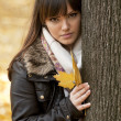 Young woman with autumn leaf in hand in autumn forest — Stock Photo