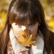 Mysterious portrait of beautiful woman hiding behind autumn leaf — Stock Photo