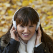 Stock Photo: Young smiling fashion woman with headphones enjoying music