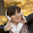 Beautiful smiling woman listening to music and dancing — Stock Photo