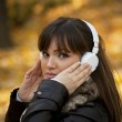 Portrait of a beautiful girl listening to music in autumn park — Stock Photo #8566566