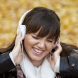 Closeup portrait of a beautiful happy woman listening to music — Stock Photo #8566618