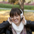 Portrait of a beautiful smiling woman listening to music and dan — Stock Photo