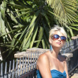Stock Photo: Attractive blond girl with sunglasses posing near palm tree