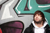 Young man posing in front of a colorful graffiti wall — Stock Photo