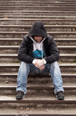 Sad teenage boy with hood sitting on stairs — Stock Photo