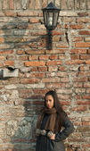 Beautiful woman leaned against brick wall — Stok fotoğraf