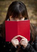 красивая девушка, прячась за книгу — Стоковое фото