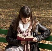 Bela mulher sentada num banco de parque e ler um livro — Foto Stock