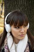Joven mujer atractiva con auriculares escuchando música en el parque un — Foto de Stock