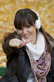 Portrait of a beautiful smiling woman listening to music with th — Stock Photo
