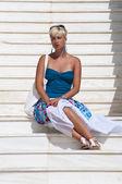 Schöne blonde frau sitzt auf der treppe — Stockfoto