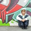 Girl sitting on floor near graffiti wall — Stock Photo #8570602