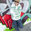 Girl standing in front of a graffiti wall — Stock Photo #8570982