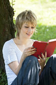 Portrait of beautiful woman reading in nature — Stockfoto